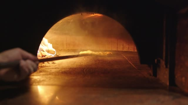 Chef using a peel to move around the pizza baking in wood fired oven video