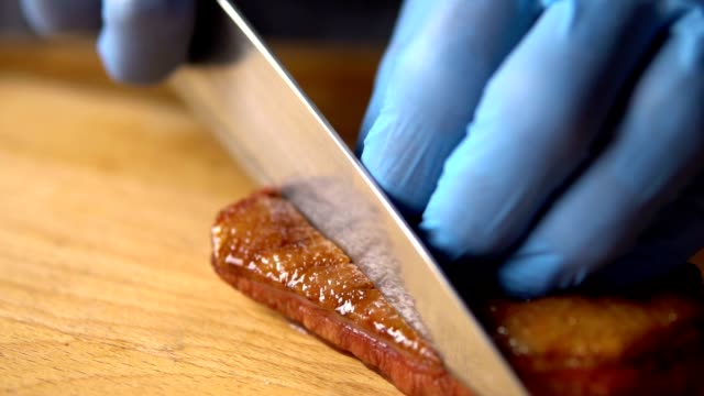 a chef with a large knife cuts grilled on charcoal duck breast - утка водоплавающая птица стоковые видео и кадры b-roll