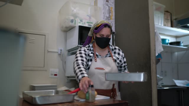 Chef woman cooking in a commercial kitchen - wearing face mask Chef woman cooking in a commercial kitchen - wearing face mask mid adult women stock videos & royalty-free footage