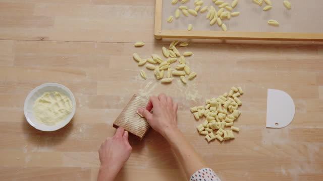 Chef woman's hands making gnocchi pasta