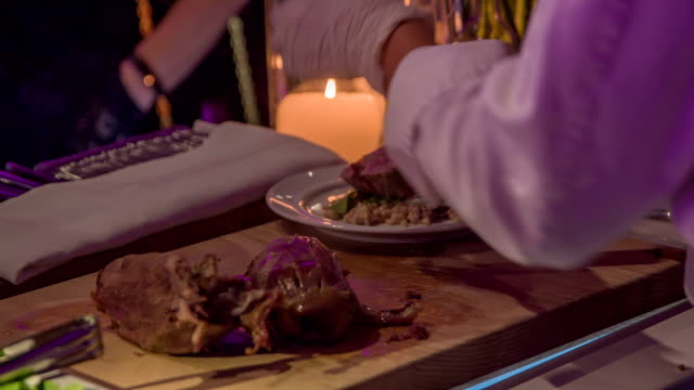 Chef`s assistant putting a slice of delicious roasted pork`s leg on a plate