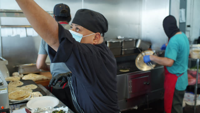 vídeos de stock e filmes b-roll de chefs cooking mexican cuisine wearing masks and gloves at work during covid-19 lockdown - covid restaurant