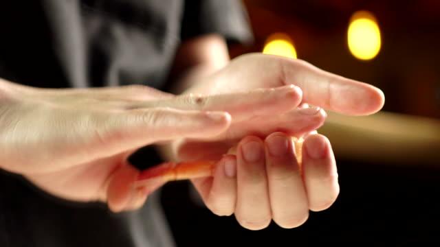 Chef's hand, making Nnigiri Sushi at the kitchen at the Japanese restaurant