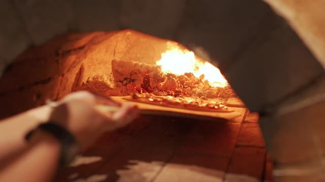 vídeos de stock, filmes e b-roll de mão do chef levando pizza no forno de barro - comida italiana