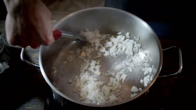vídeos y material grabado en eventos de stock de la mano masculina del chef pone las cebollas picadas en una cacerola con aceite vegetal. 4k - cebolla