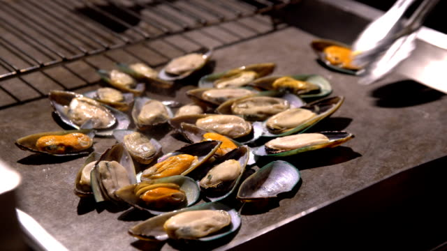 Chefs prepare clams in a restaurant in the open air in the evening. video