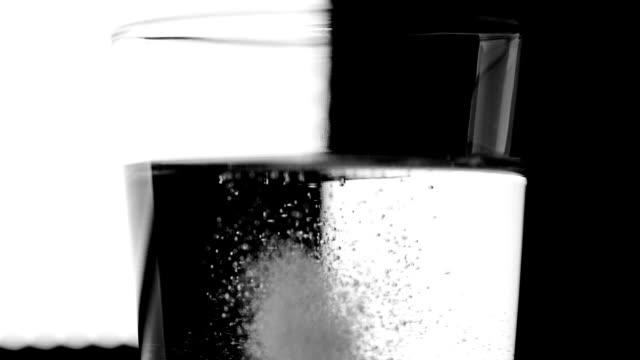 chemical reaction pill dissolving in water - vitamin d stok videoları ve detay görüntü çekimi