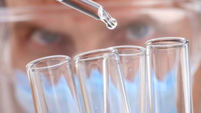 vídeos y material grabado en eventos de stock de químico haciendo ciencia experimento con sustancias químicas. close-up. - investigación científica