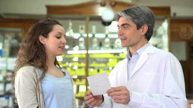 Chemist explaining medication to female customer Mature pharmacist explaining medication to female customer. Young woman talking to male chemist. They are in pharmacy. less than 10 seconds stock videos & royalty-free footage
