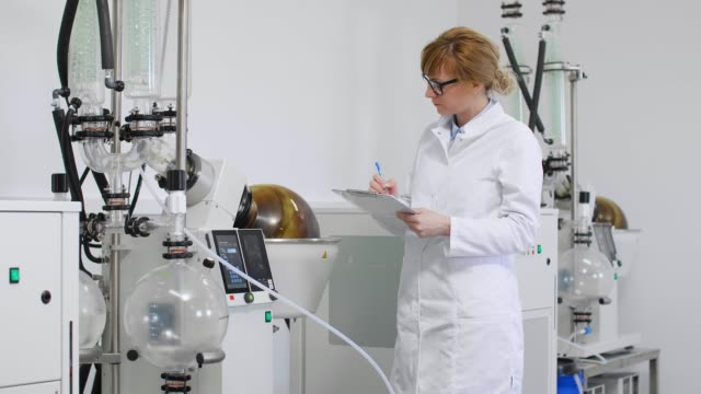 Chemist inspecting rotavapor machine in laboratory and writing down results. Scientist inspecting rotovapor in laboratory during CBD oil extraction. She is wearing rubber gloves and standing next to rotational vaporizer with green condenser. cbd oil stock videos & royalty-free footage