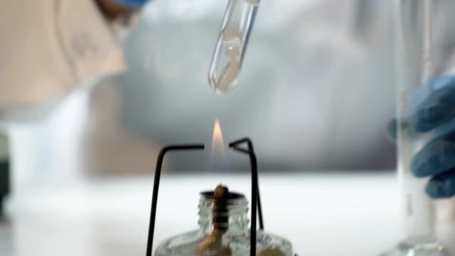 Chemist pouring boiling fuming liquid into test tube, conducting experiment video