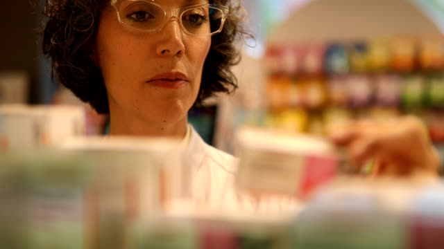 Chemist searching for medicine on shelves in store Mature chemist searching for medicines on shelves. Female pharmacist is wearing eyeglasses. She is working in pharmacy. pharmacist stock videos & royalty-free footage