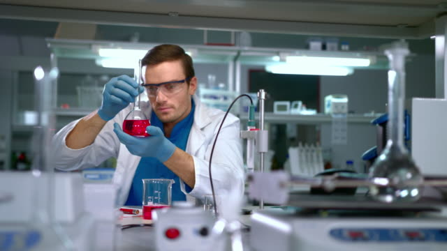 chemist studying liquid in glass flask at modern lab. laboratory worker - reagente video stock e b–roll