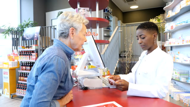 Chemist talking over prescription with customer Female chemist and customer talking over prescription medicine. Professional is advising senior woman. They are standing at checkout counter in pharmacy. pharmaceutical industry stock videos & royalty-free footage