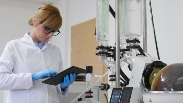 실험실에서 로타바포 기계 옆에 태블릿에서 작업하는 화학자 - 칸나비디올 스톡 비디오 및 b-롤 화면