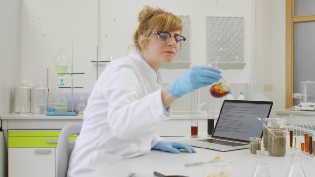 Chemist working with hemp CBD oil in laboratory and writing results in laptop. Chemical scientist working with hemp CBD and CBDa oils in laboratory. She is writing results in laptop, using glass tubes and erlenmeyer flasks. Healthcare pharmacy from cannabis seeds. cbd oil stock videos & royalty-free footage