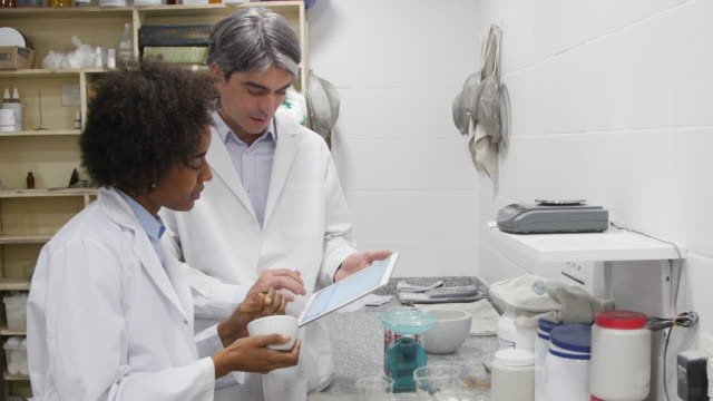 Chemists with tablet PC making pills at pharmacy Mature pharmacist using digital tablet while coworker making medicine with mortar and pestle. Male and female chemists discussing while working in pharmacy. They are wearing lab coat. mortar and pestle stock videos & royalty-free footage