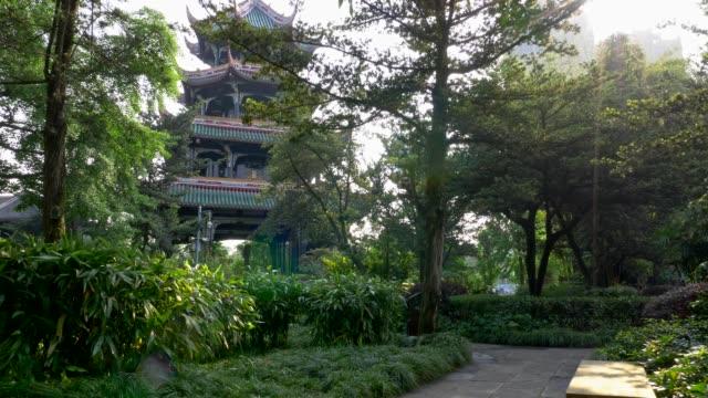 成都, 四川省, 中国。迭タワー (迭パビリオン) と緑豊かな緑の植物。迭パビリオン公園で木 々の間から太陽の日差し。タワーが背景にあります。4 k - 仏塔点の映像素材/bロール