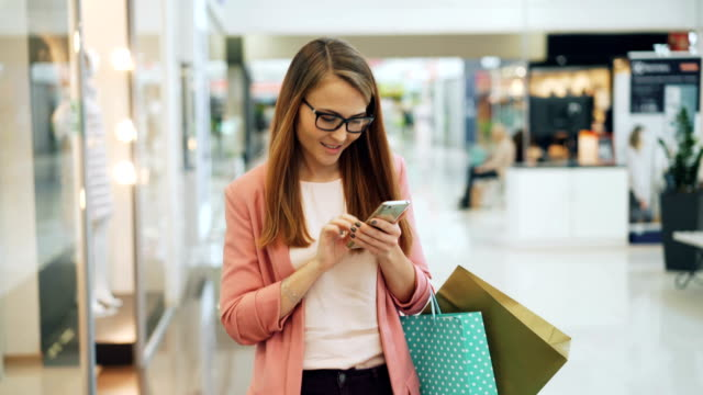 Cherful young woman is using smartphone in shopping center touching screen then looking around at new collection of clothing holding paper bags. Youth and gadgets concept.