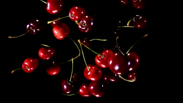 Cherry bouncing against to the camera Cherry bouncing against to the camera on a black background in slow motion cherry stock videos & royalty-free footage