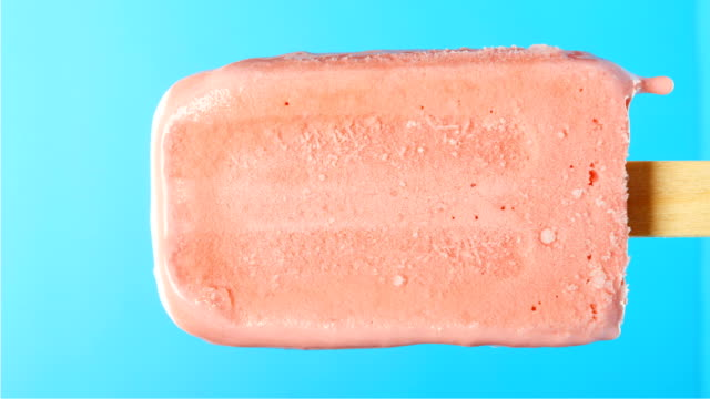 cherry flavor popsicle melting on blue timelapse please rotate it at 90 degrees to get a vertical composition - vídeo