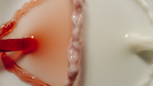 SLOW MOTION:  Cherry juice and milk mixing together - Top View