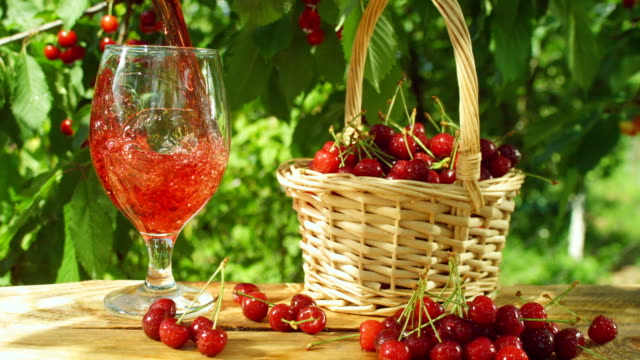 Cherry juice poured in to wine glass. Beautiful fresh, ripe, juicy red cherry cherries in wicker basket on the wooden table. Cherry juice poured in to wine glass. cherry stock videos & royalty-free footage