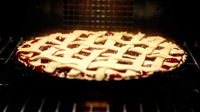 vídeos de stock e filmes b-roll de cherry pie cooking in oven - assado no forno