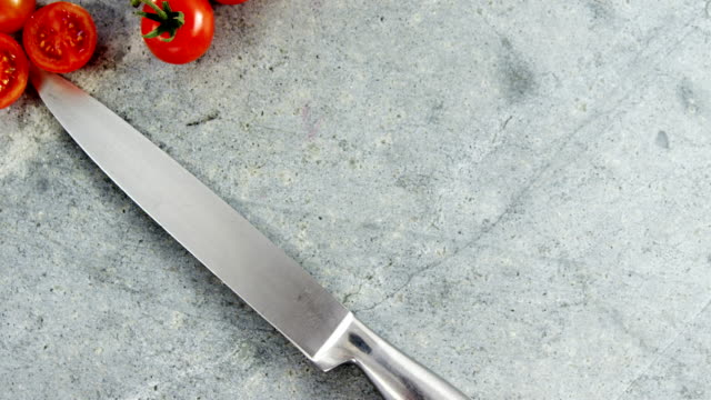 Cherry tomatoes and kitchen knife on concrete video