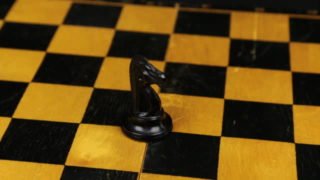 Chess black horse figure in a middle of playing board close-up. Rotation. Chess figures