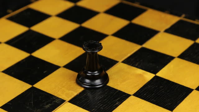 Chess black rook figure in a middle of playing board close-up. Rotation. Chess figures