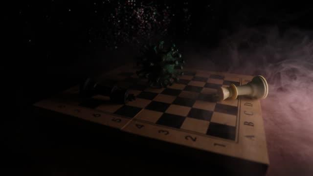 schachbrettspiel konzept strategie des geschäfts in covid globale pandemie. big corona virus miniatur-modell auf schachbrett mit nebel und hintergrundbeleuchtung. kreative kunstwerk dekoration. selektiver fokus - könig schachfigur stock-videos und b-roll-filmmaterial