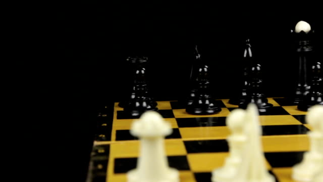Chess pieces are placed on the chessboard, the beginning of the chess game. Slider shot.