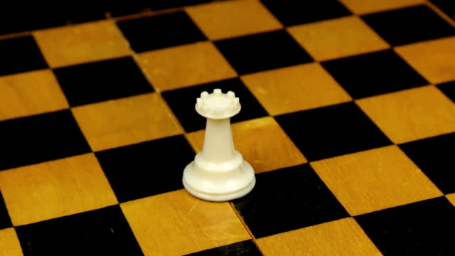Chess rook figure in a middle of playing board close-up. Rotation. Chess figures