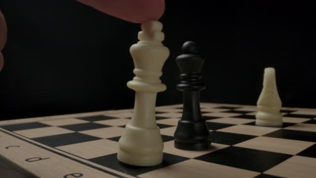 schach. der weiße könig ist von hand gefallen. schwarze siegen - könig schachfigur stock-videos und b-roll-filmmaterial