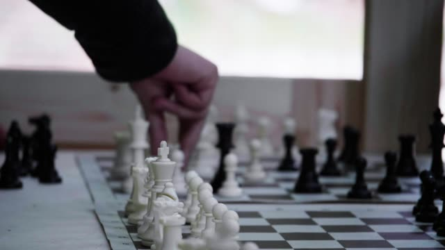 Chessboard and Chess Pieces Beautiful shot of chessboard and chess pieces in slow motion. Rack focus. positioning stock videos & royalty-free footage