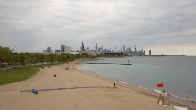 Chicago beach, Lake Michigan, and skyline shot by drone from south of the city. The shot starts low and ascends.  It was shot in the morning with an overcast sky. south stock videos & royalty-free footage