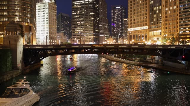 Chicago cityscape and ferry boats on the river at night