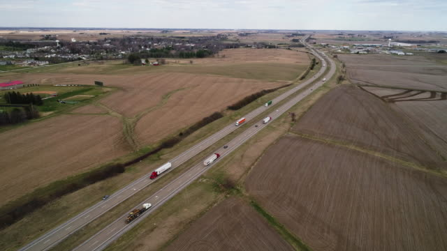 Chicago - Kansas City Expressway surrounded by the agricultural fields in the springtime, nearby Lyndon Township, Illinois, USA. Cinematic aerial drone video with the wide panoramic-orbit camera motion.