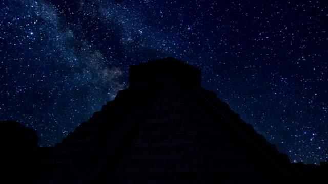vídeos de stock, filmes e b-roll de lapso de tempo de chichen itza na noite com estrelas - civilização milenar
