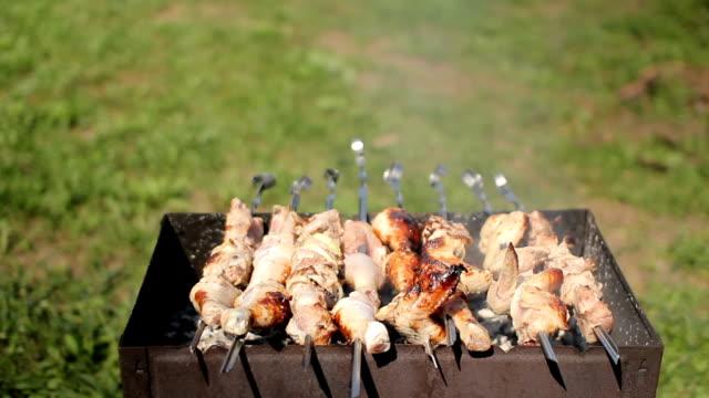 vidéos et rushes de poulet et porc grillé sur charbon de bois dans un barbecue. la viande tourne et a la peau dorée. déplacement de la caméra - haie