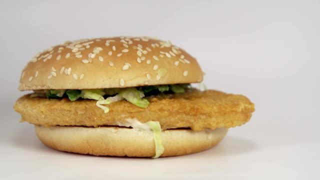 vídeos de stock, filmes e b-roll de hambúrguer de frango com pão semeado e alface caindo sobre fundo branco - junk food