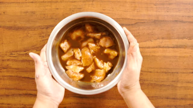 kycklingbitarna soaked för marinad på en glänsande pan - top vinkel skott - marinad bildbanksvideor och videomaterial från bakom kulisserna
