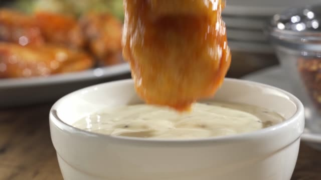 Chicken Wing Dip Delicious Buffalo style chicken wing dipped into ranch blue cheese sauce. animal wing stock videos & royalty-free footage