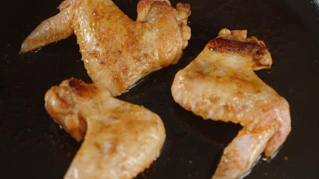 vidéos et rushes de les ailes de poulet sont frites dans une poêle avec des bulles d'huile. - croustillant
