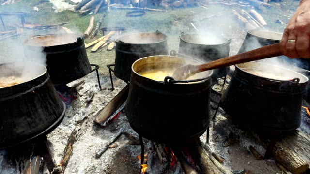 Chief cook and stir a stew in cauldrons and kettle upon fire at tourist summer camp video