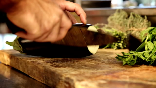 Chief cutting an eggplant. Close up video