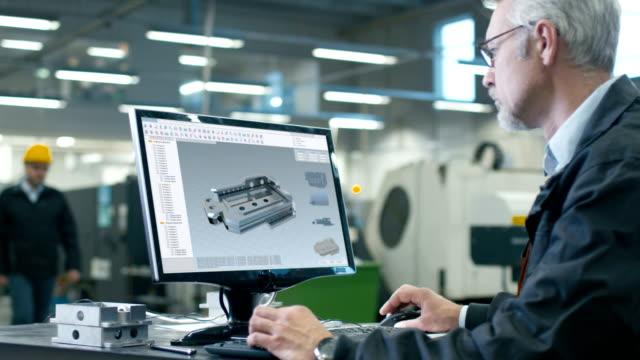Şef Mühendis kişisel bilgisayar, mekanik ayrıntılı olarak CAD tasarımı üzerinde çalışıyor. O büyük fabrikada çalışıyor. video