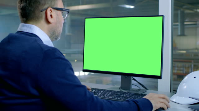 Chief Engineer Works on His Computer with Mock-up Green Screen. Inside of the Factory is Seen From Her Office Window.