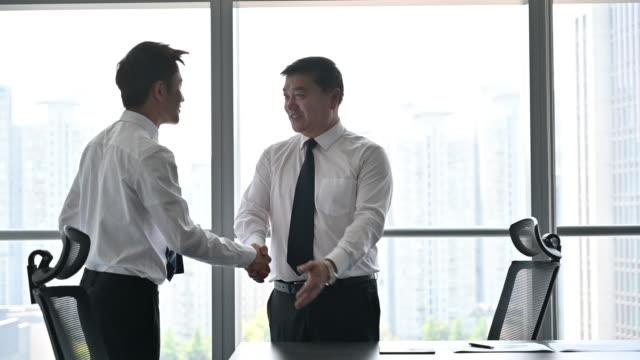 最高経営責任者は若いビジネスマンと握手 - テーブル点の映像素材/bロール